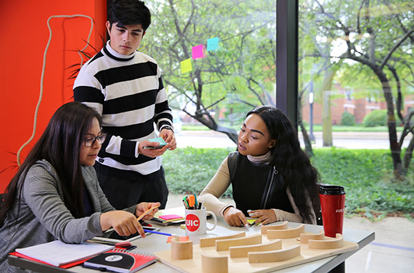Two female and one male student work together around a table.
