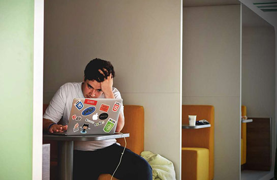 A male student looking at a laptop screen in a state of distress