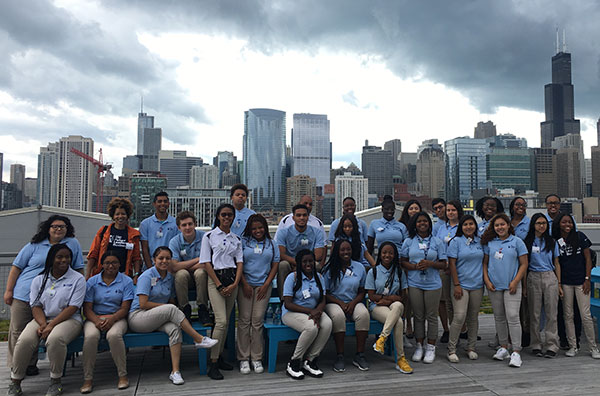 Students siting outside with the Chicago skyline in the background.