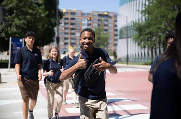 Students crossing the street on campus, smiling and giving a thumbs up.
