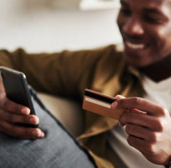 Man holding a cell phone and a credit card