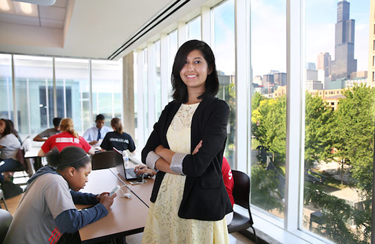 Female UIC student standing up and smiling while in class
